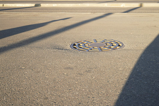 Iron round manhole lies on the pavement. In the city sewer closes the hatch.  Sity