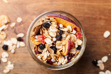 Granola, muesli in glass jar. Healthy breakfast. Organic oats with berries and nuts. Close up.