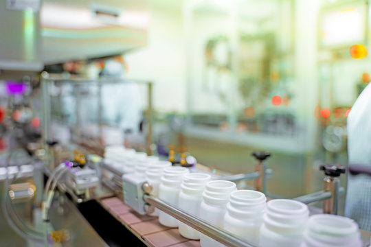 Transfer medicine bottles on the conveyor belt in the pharmaceutical industry, industrial machinery for the quality of medical products. Industrial concept and factory technology.shallow focus effect.