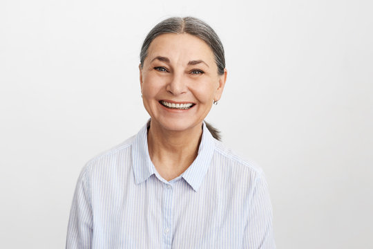 Joy, happiness, aging, old people and positive vibrations concept. Picture of happy elegant senior 65 year old female in good mood wearing blue shirt looking at camera with broad cheerful smile