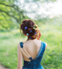 unusual cool chic hairstyle with flowers for long dark hair, work of hairdresser, gentle image for graduation and wedding, forest nymph in water colored dress, art photo from back without face
