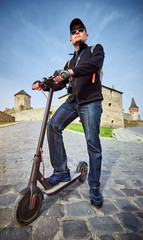 A man rides a scooter in the countryside in summer.