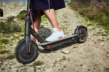 Girl riding a scooter in the countryside in summer.