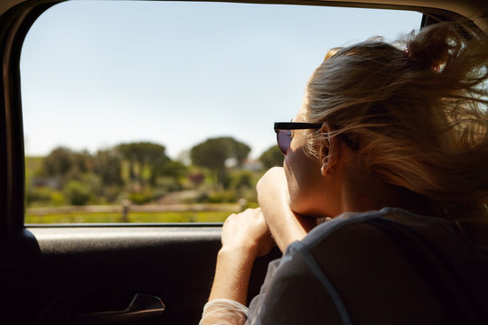 Back shot of attractive blonde European woman wearing sunglasses sitting inside car with open window, enjoying road trip, looking out, admiring beautiful summer views. People and lifestyle concept