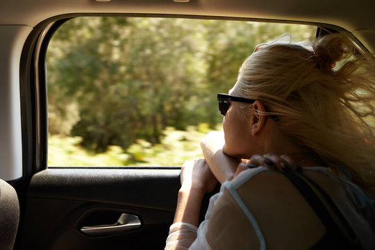 Stylish blonde female in shades sticking out head out of window while sitting in back seat, traveling by car, her hair flying in wind. Freedom, road trip, travel, adventure and transportation concept