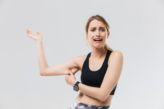 Image of disappointed blond woman 20s dressed in sportswear crying while touching her fat arm during workout in gym is