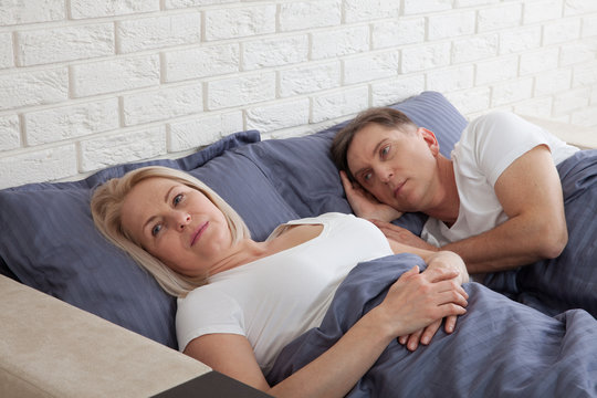 Unhappy middle aged couple in bedroom at home