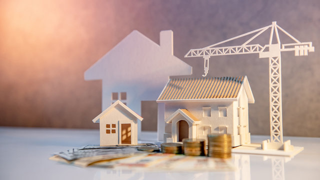 Real estate or property development. Construction business investment concept. Home mortgage loan rate. Coin stack on international banknotes with house and construction crane models on the table.