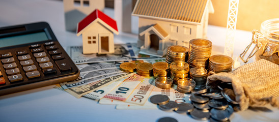 Real estate development or property investment concept. Home mortgage loan rate. Coin stack on international banknotes with house models and calculator on the table.