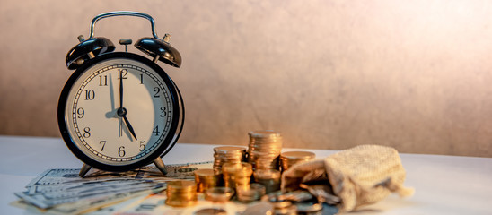 Table clock and gold coin stack on the table with international banknotes currency. Time investment...