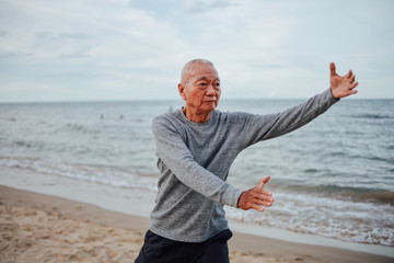 Asian Senior old man practice Tai chi and Yoga pose on the beach sunrise