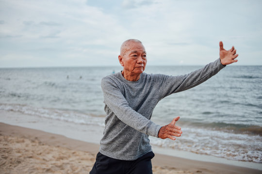 Asian Senior old man practice Tai chi and Yoga pose on the beach sunrise