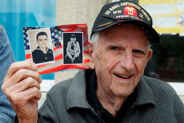 World War II veteran Cliff Goodall poses with a picture of himself in uniform as a young seaman, on the Normandy coast ahead of the 75th D-Day anniversary, in Montebourg