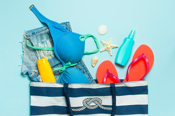 Wall Mural - Summer sea accessories. Beach bag Coral flip flops swimsuit denim shorts shells starfish sunscreen bottle body spray on blue background top view flat lay. Summer background. Holiday travel concept.