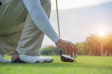 Man hand putting golf ball on tee in golf course - Image