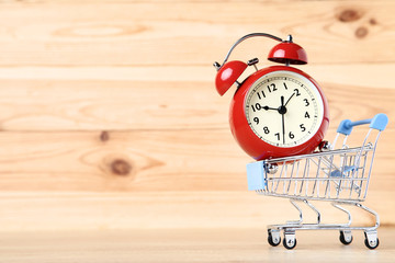 Small shopping cart with alarm clock on brown wooden table