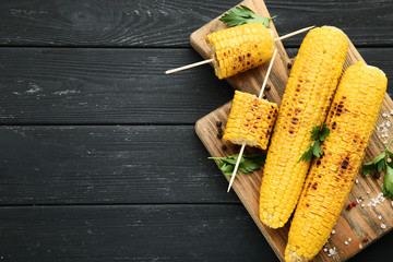 Grilled corn with parsley and seasonings on black wooden table
