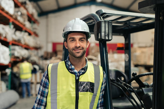 Smiling worker standing by his forklift in a warehouse
