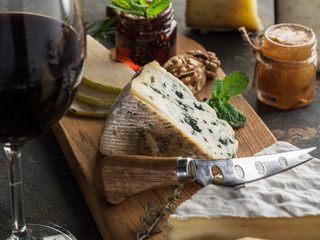 Wall Mural - Cheese platter with blue cheeses, fruits, nuts and wine on stone background. Tasty cheese starter.