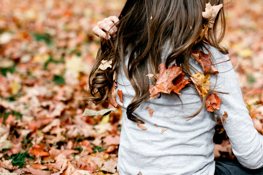 Girl's hair with leafs in forest, autumn season