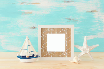 Nautical concept with empty photo frame and sail boat over wooden table. For photography montage