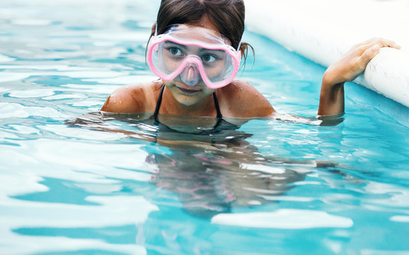 Little girl in swimming pool wearing goggles