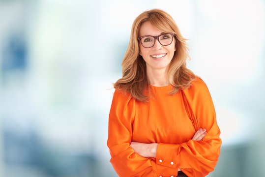 Portrait of executive middle aged businesswoman looking at camera and laughing
