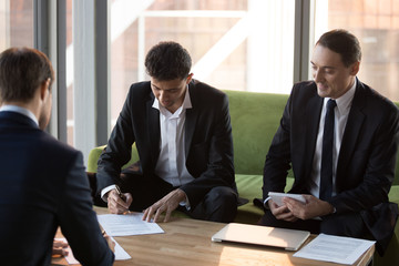 Businessmen sign business contract after successful negotiations