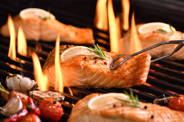 Fototapete - Grilled salmon fish with various vegetables on the flaming grill