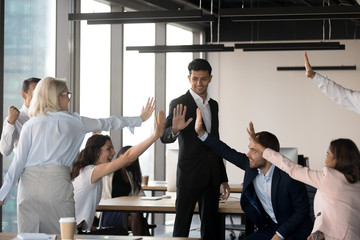 Excited team give high five celebrating shared success in office