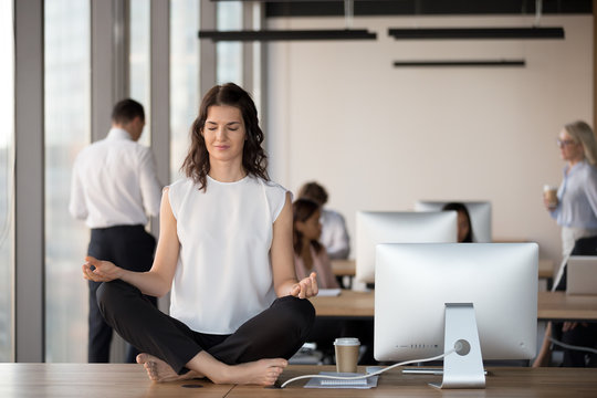 Calm female employee practice yoga on table in coworking space