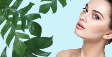 Wall Mural - Woman face with fresh smooth skin, clean face and blue eyes with tropical green leaf on background