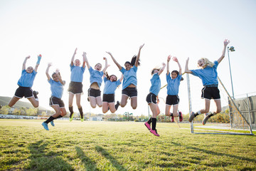 Happy girls in soccer uniforms with arms raised jumping on grassy field against sky
