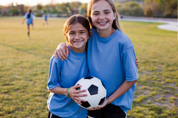 Portrait of smiling friends holding soccer ball in grassy field
