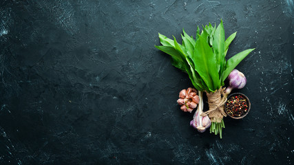 Fototapete - Fresh wild garlic leaves on black background. Wild leek. Top view. Free space for your text.