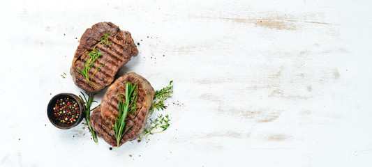 Tuinposter Steakhouse Grilled ribeye beef steak, herbs and spices on a white wooden background. Top view. Free space for your text.