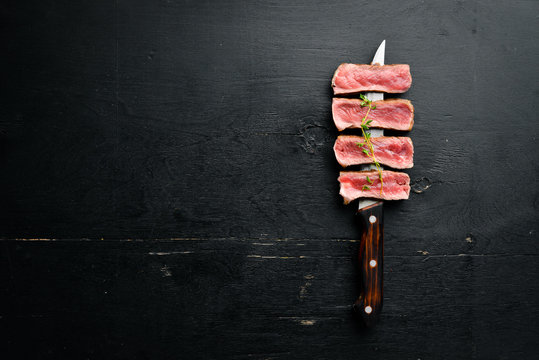 Juicy Steak on the knife. Top view. Free space for your text.