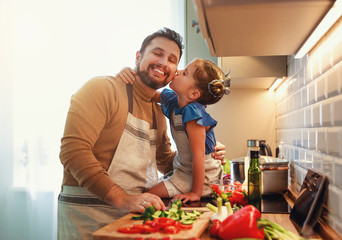 happy family father with child daughter preparing vegetable salad .