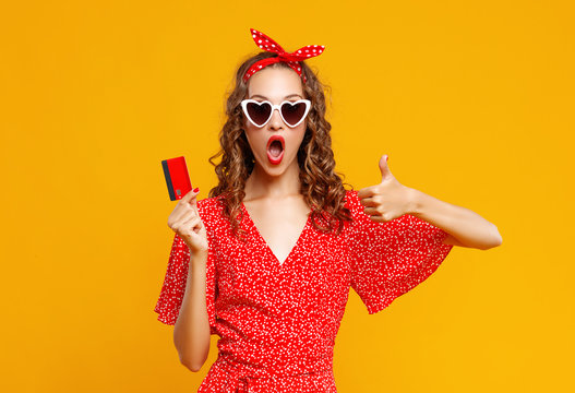 beautiful funny girl  with plastic credit card for shopping for yellow color background.