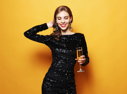 lifestyle, party and people concept: beautiful girl in a cocktail dress holding a glass of champagne