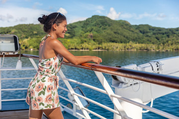 Wall Mural - Cruise ship vacation woman relaxing in sun enjoying boat deck resting on railing of looking at Tahiti island landscape. Happy Asian girl on French Polynesia holiday travel.