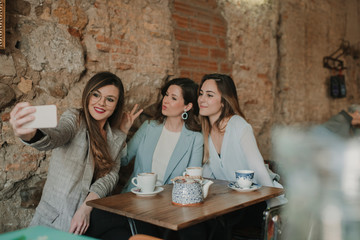 Three young women taking a selfie in a cafe
