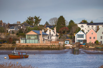Houses on the banks of the river Exe in Topham. An old fishing boat in the foreground is moored. Devon. UK