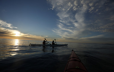 Kayakers take in the last of the days light as cold front moves in off Cape Town