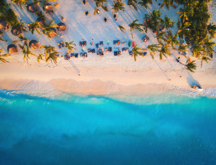 Poster Zanzibar Aerial view of umbrellas, palms on the sandy beach of Indian Ocean at sunset. Summer travel in Zanzibar, Africa. Tropical landscape with palm trees, parasols, people, sand, blue water, waves. Top view