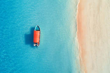 Aerial view of the fishing boat in clear blue water at sunny day in summer. Top view from the air...