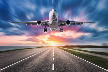 Poster Avion à Moteur Airplane and road with motion blur effect at sunset. Landscape with passenger airplane is flying over asphalt road and colorful sky. Commercial plane is landing. Aircraft with blurred background
