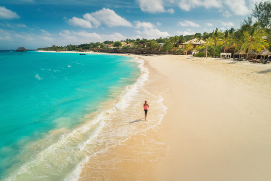 Aerial view of the running young woman on the white sandy beach near sea with waves at sunny day. Summer holiday. Top view of sporty slim girl, clear azure water. Indian Ocean. Lifestyle and sport