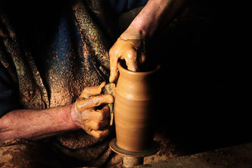 Close up mud covered hands of adult man making clay pot on potter's wheel Fototapete