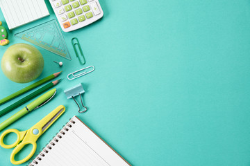 Education or back to school Concept. Top view of Colorful school supplies with books, color pencils, calculator, pen cutter clips and apple on green pastel background. Flat lay. Wall mural